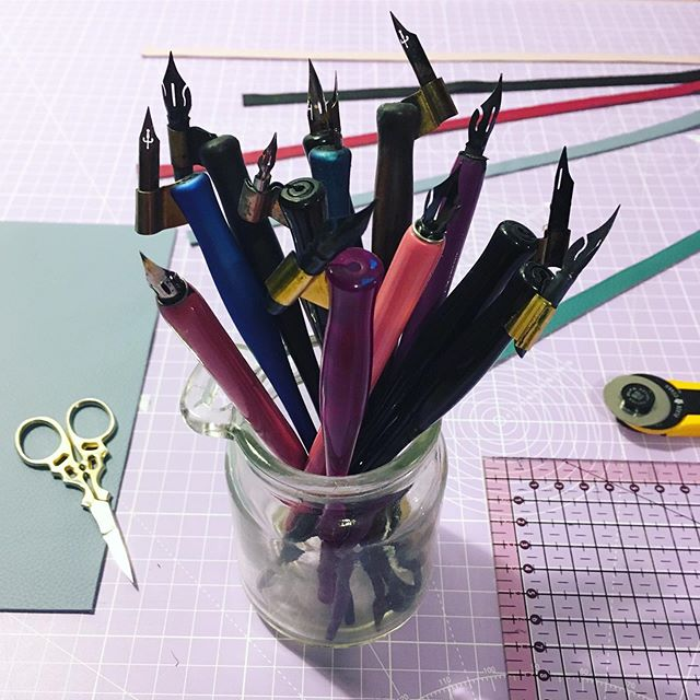 #whatsonmydesk I'm not used to seeing all my pens in a jar!!! They live safely in my pen roll. I love my pen roll I made it years ago and I love how the leather has softened with time. How I never have to worry about breaking a nib! Now I've made my new design, a variation to the original. I've decided I should try it out for myself, just which colour for me!! . #daniellelummispenroll #moderncalligraphy #calligrapher #pointedpen #obliquepenholder #calligraphy