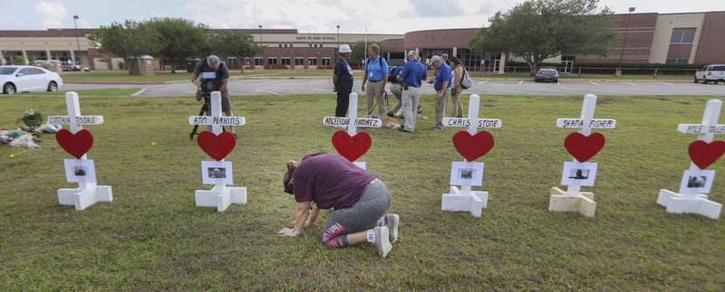 "1.       Santa Fe, Texas, resident, Lori Simmons prays for healing in front of 10 wooden crosses at Santa Fe High School on Monday, May 21, 2018, in Santa Fe. Republican Gov. Greg Abbott reacted to the killings of eight students and two teachers by calling for a series of roundtable discussions on school safety, starting with one on Tuesday in Austin. He said last week that he wants to find ways to keep guns away from those who pose an ""immediate danger to others."" (Steve Gonzales/Houston Chronicle via AP)"