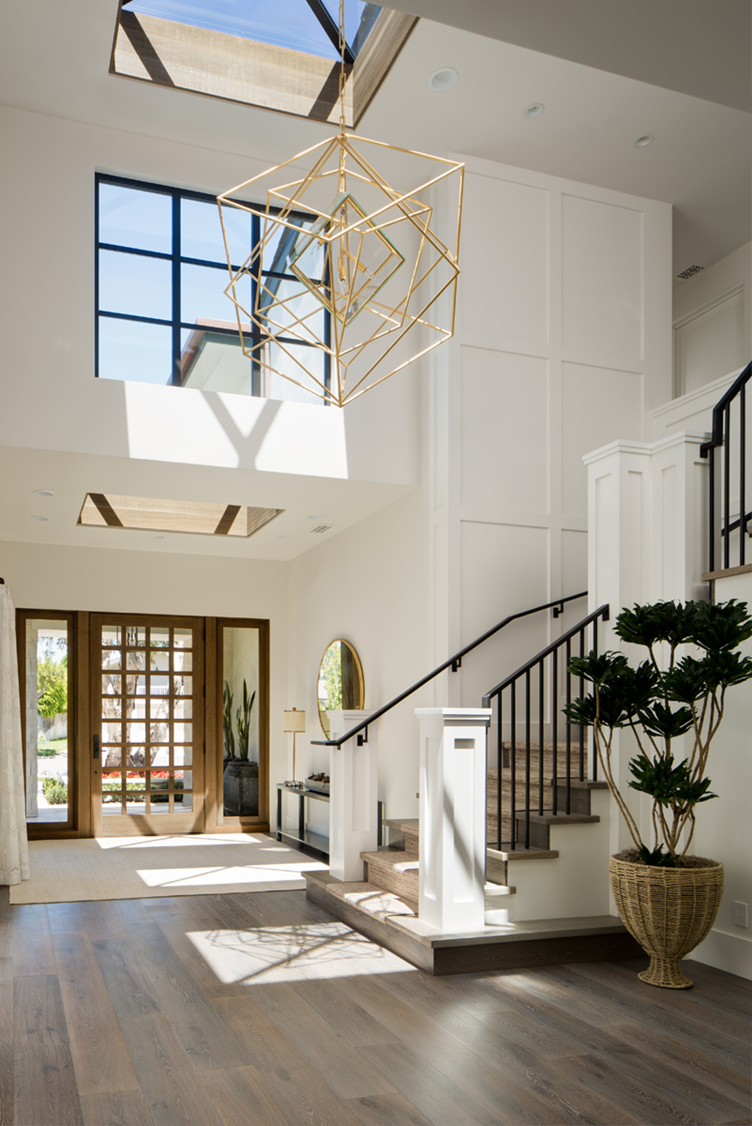 This light 'n airy Key West home by Brooke Wagner Design perfectly executes a grounding iron stair balustrade with a contrasting funky satin gold light fixture. Love! Image Via Brooke Wagner Design
