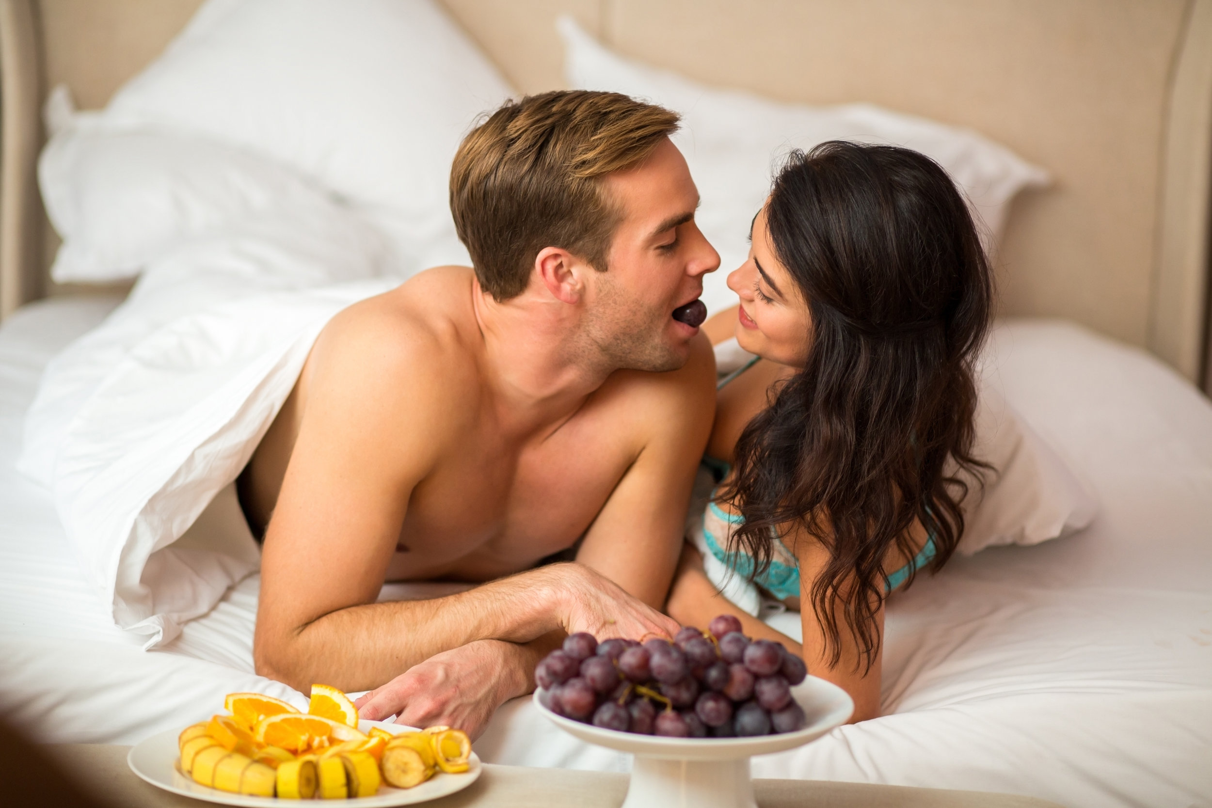 COUPLE FEEDING EACHOTHER FRUIT IN BED.jpeg
