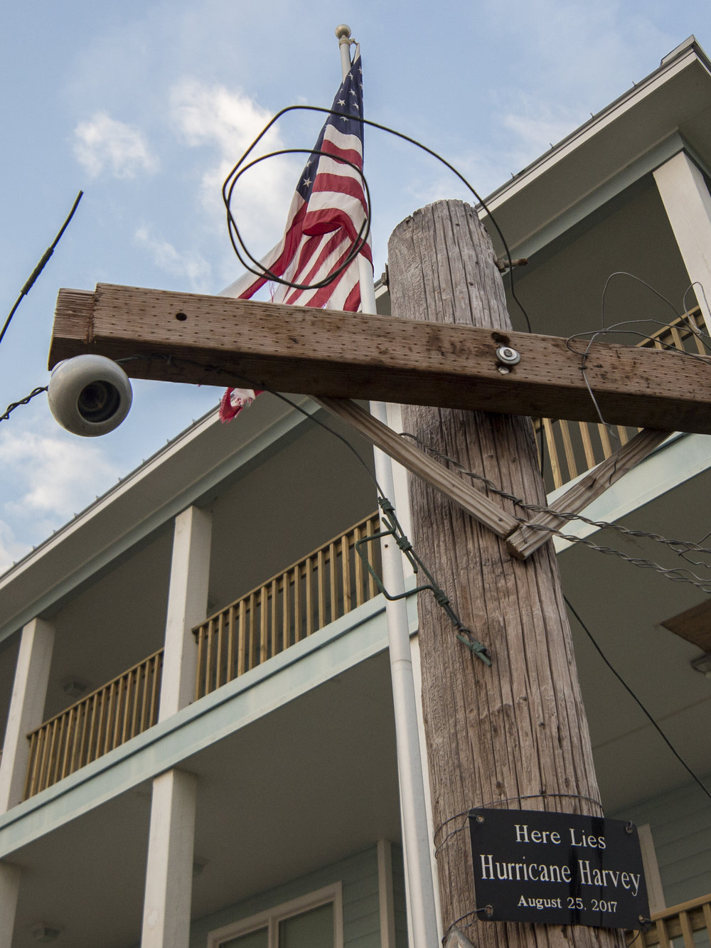 Through the coastal winds a tethered flag still waves over a makeshift epitaph, the twisted wood forms a cross. The site stands amid a ravaged landscape caised by Hurricane Harvey, 909 South Water Street.