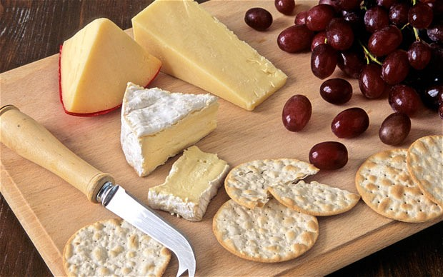 Cheese next to crackers and grapes