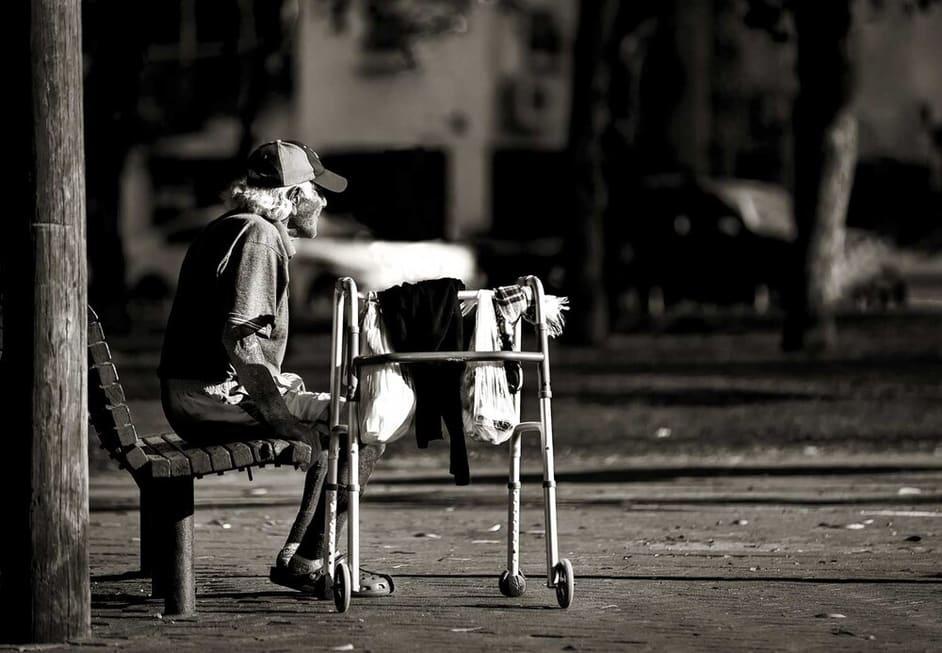 צילום רחוב שבו מופיע אדם מבוגר על ספסל