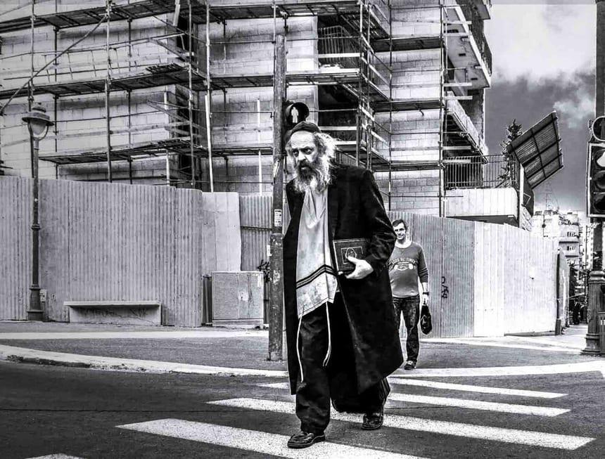 צילום רחוב שבו רואים אדם חרדי מבוגר חוצה את המדרכה