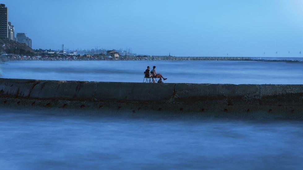 צילום אומנותי של זוג שיושב על גשר בים