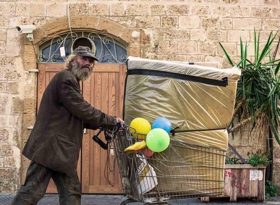 צילום רחוב שבו ניתן לראות אדם מבוגר הולך עם עגלה