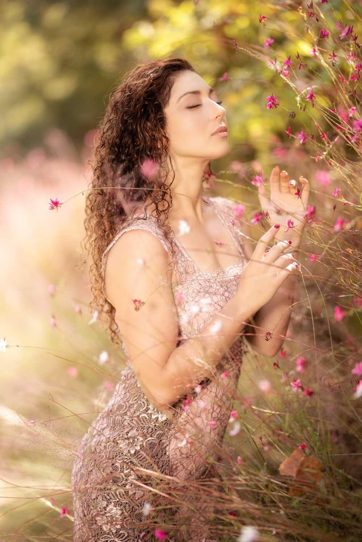 צילום חוץ של מודלית צעירה שמריחה פרחים