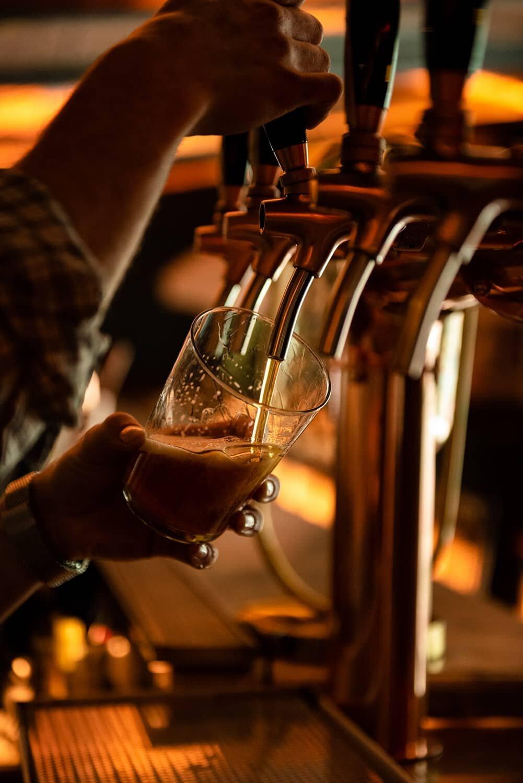 צילום של ברמן מוזג בירה במסעדה