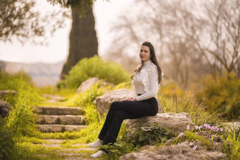 נערה יושבת באזור שופע טבע