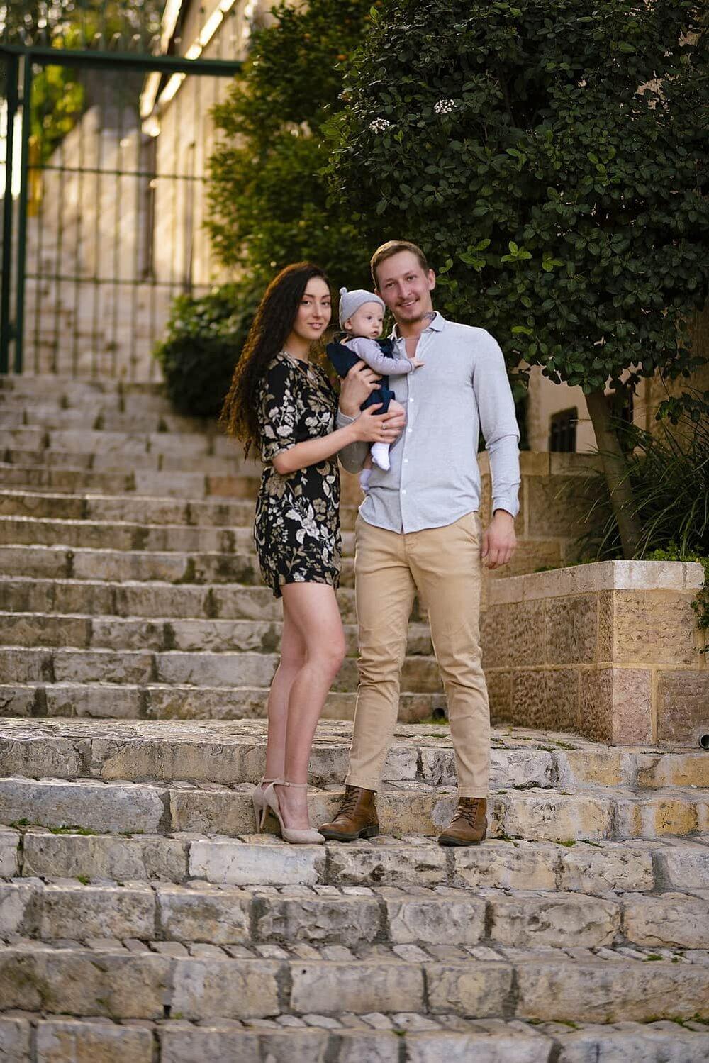 זוג צעיר עומד במדרגות עם תינוק