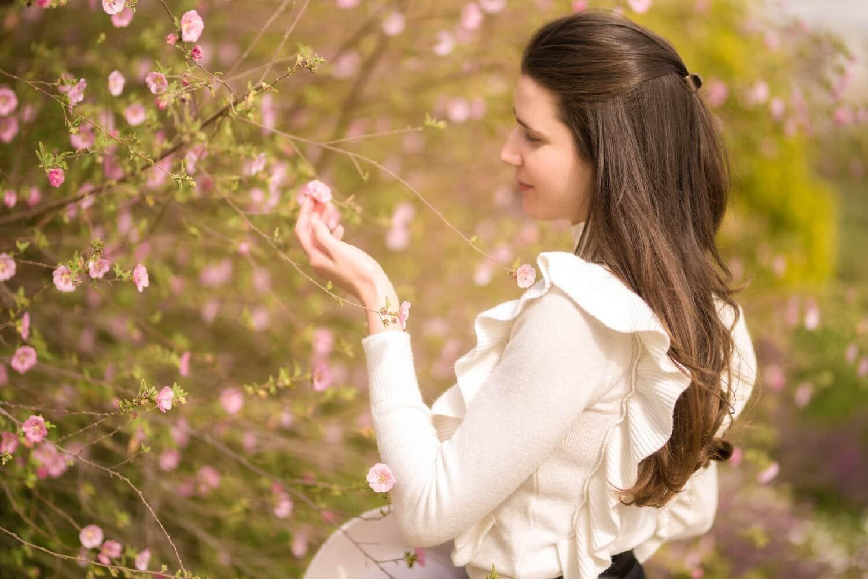 נערה בלבן ליד שיח פרחים