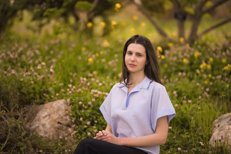 נערה יושבת במקום מוקף בטבע