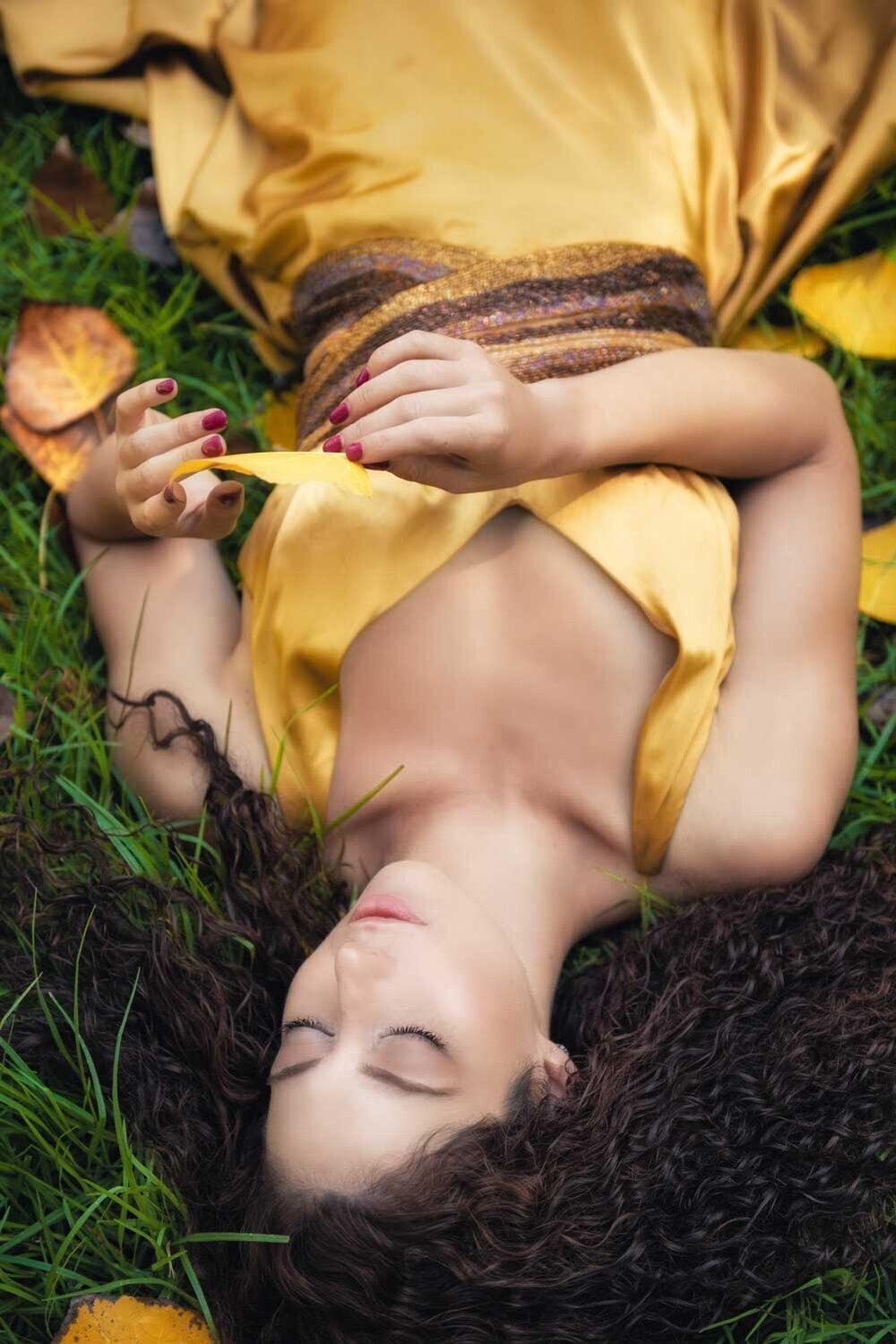 בחורה בשמלת זהב שוכבת הפוך על הדשא
