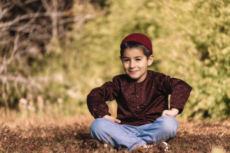 ילד יושב על הדשא ומחייך