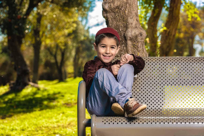 ילד יושב על ספסל ומחייך