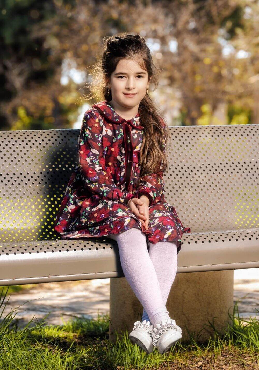 ילדה יושבת על ספסל ומחייכת