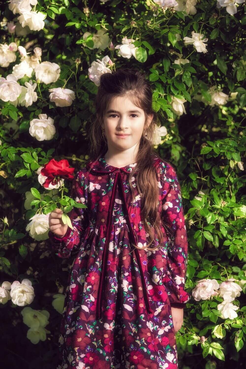 ילדה מחזיקה פרח אדום ומאחוריה שיח ורדים