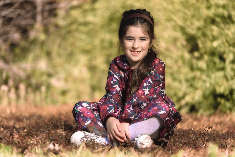 ילדה יושבת על דשא ומחייכת