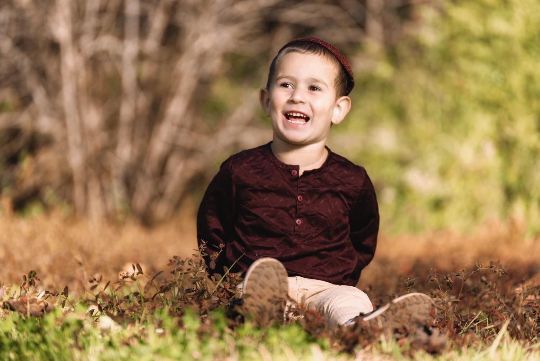ילד קטן יושב על דשא ומחייך