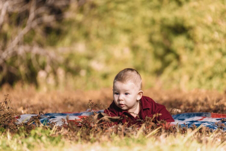 תינוק חמוד ששוכב ליד דשא