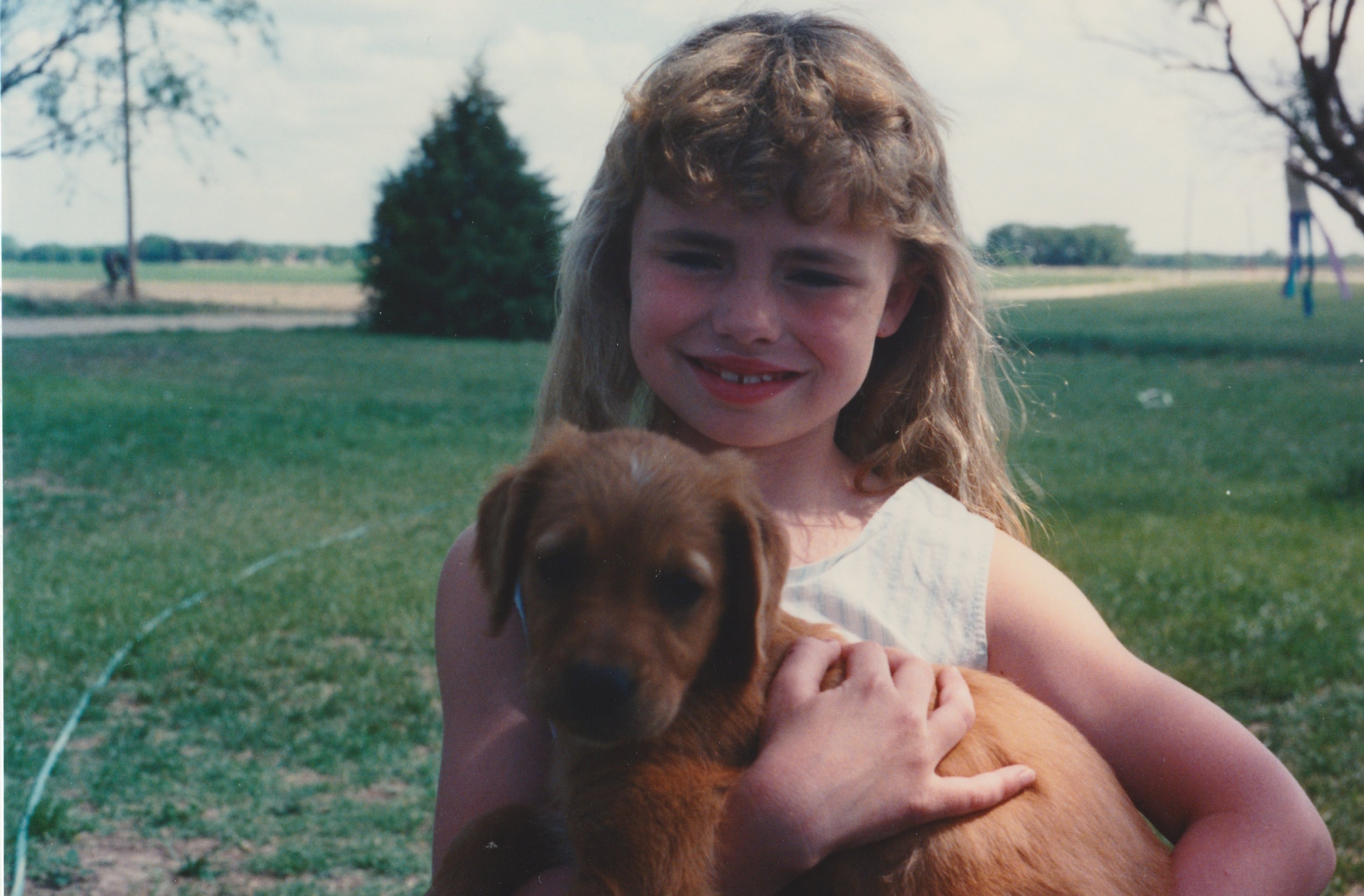 Little Lindsay with sunburnt cheeks, a sprinkler, and a dog named Penny.