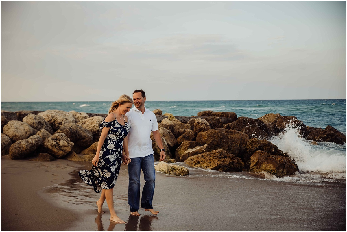 couple walking on beach laughing