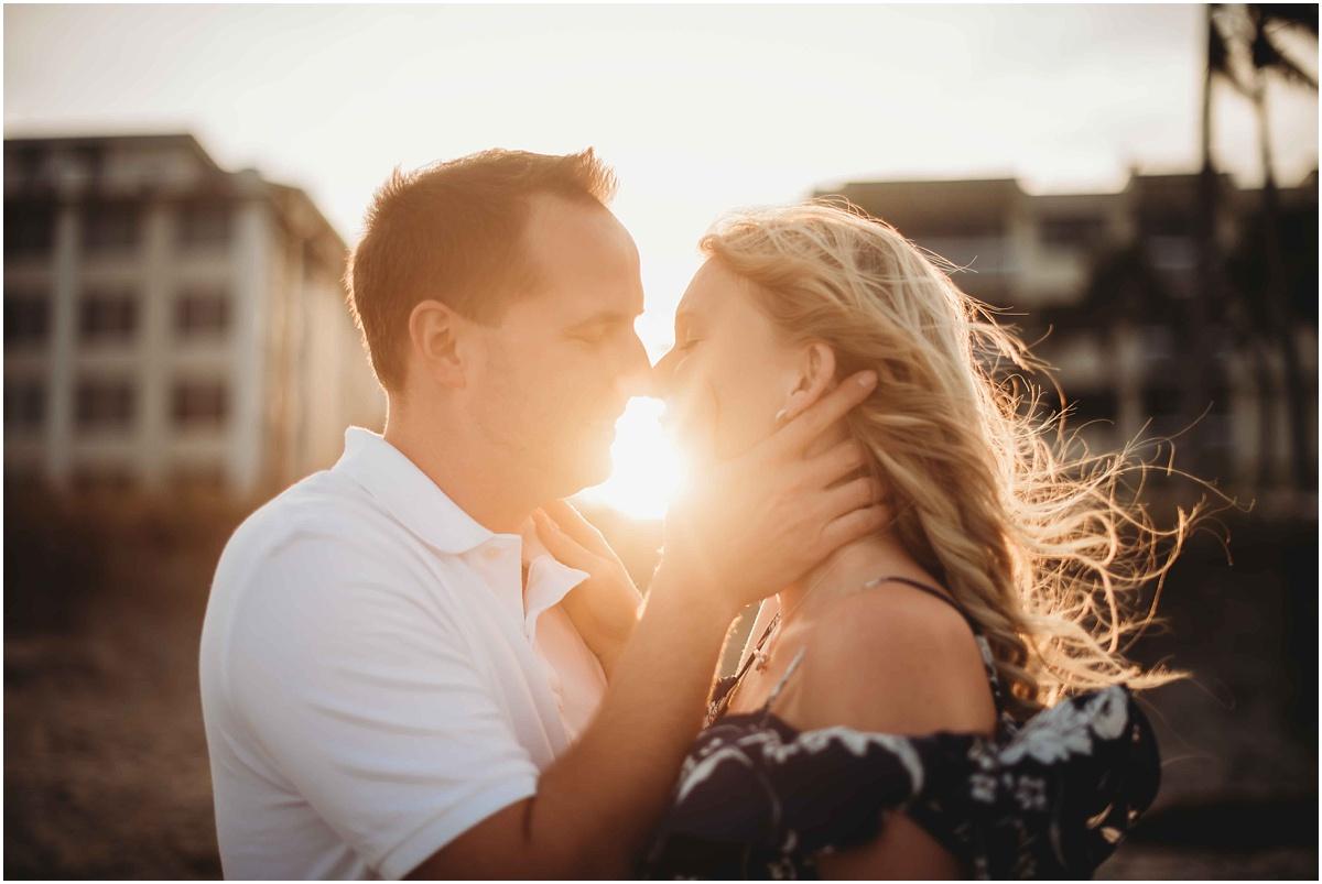 couple kissing sunlight peeking through