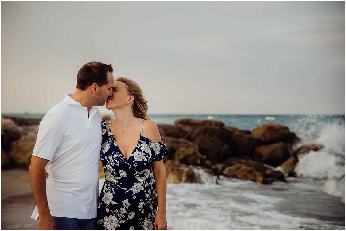 couple kissing waves crashing on beach