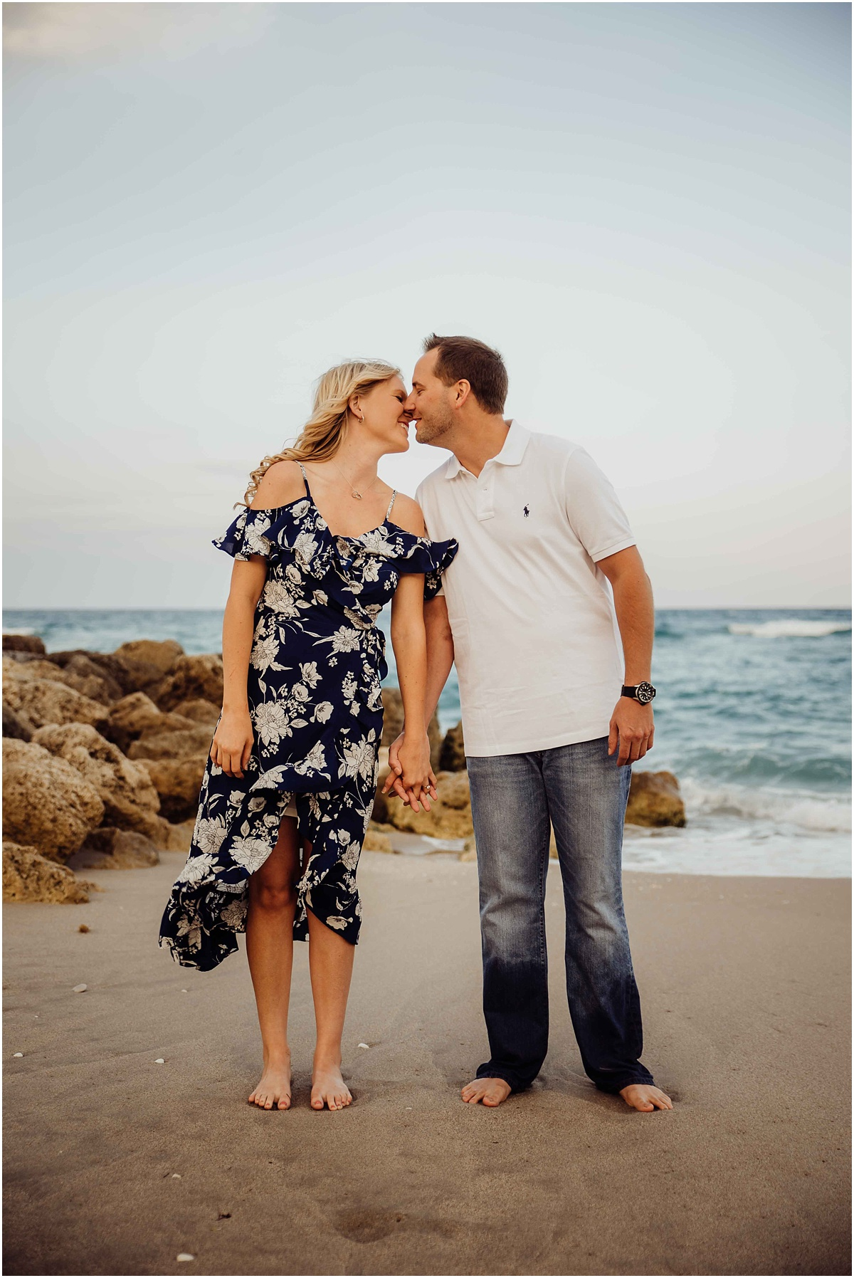 couple kissing on the beach blue and white attire