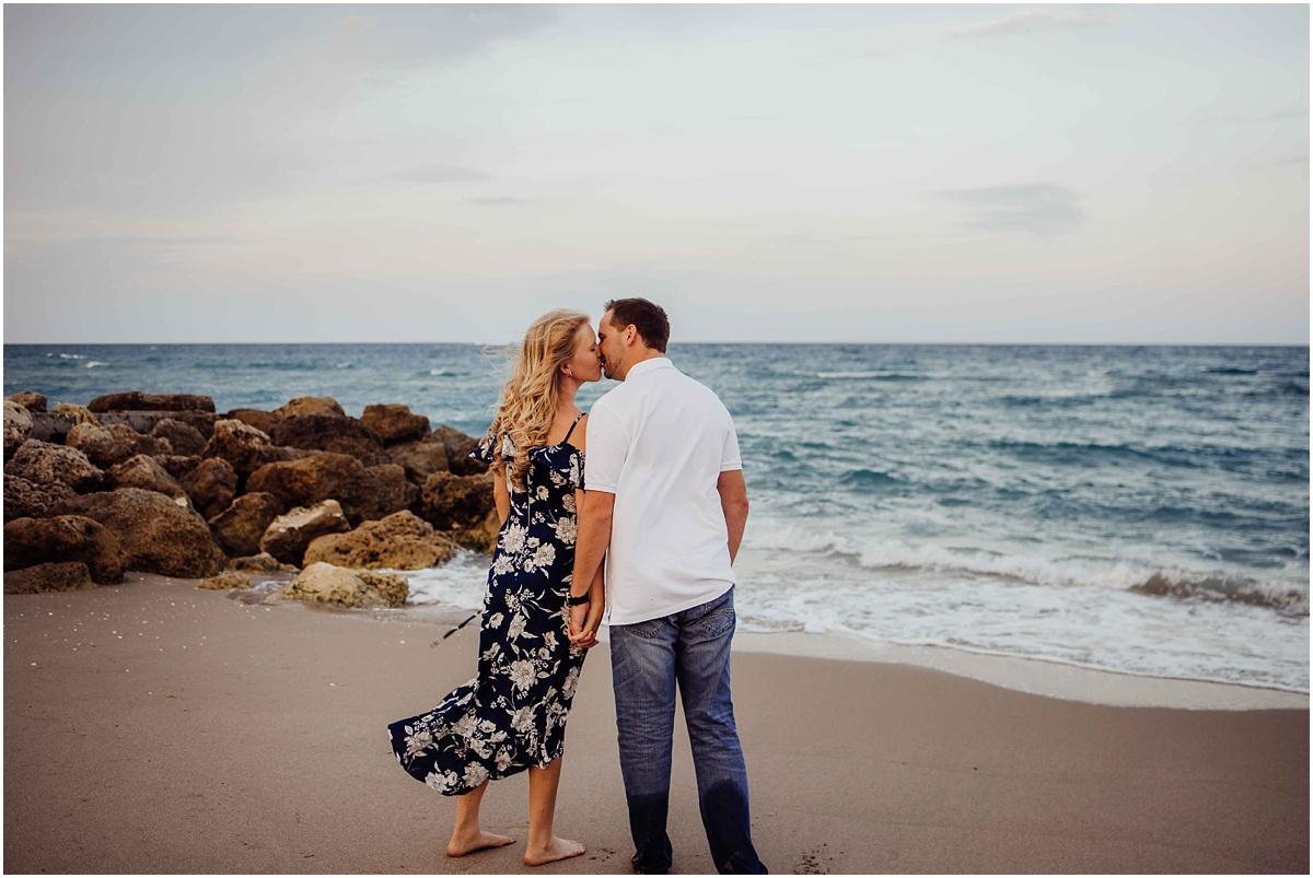 couple facing beach kissing