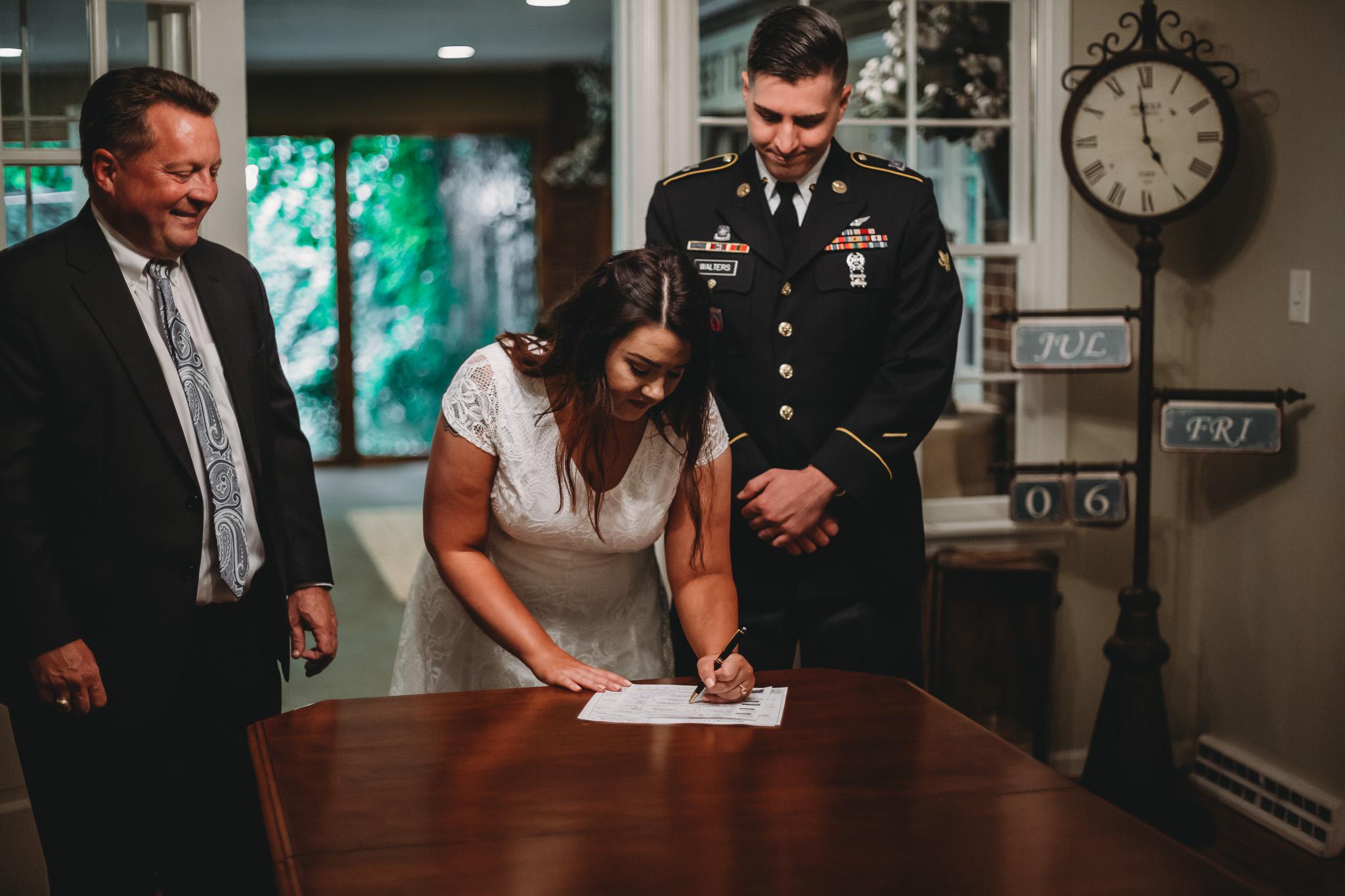 bride signing wedding paperwork