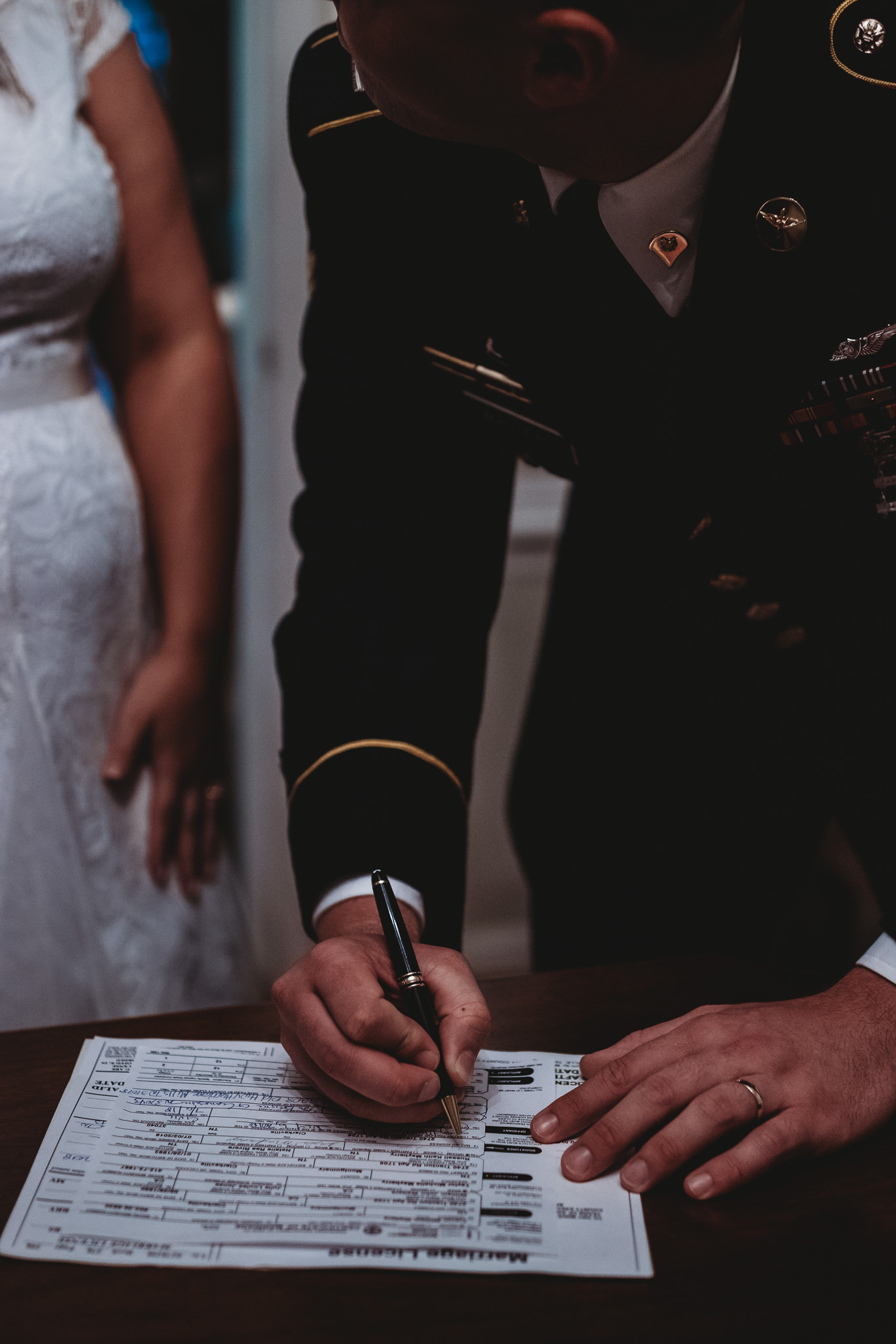 groom signing wedding paperwork