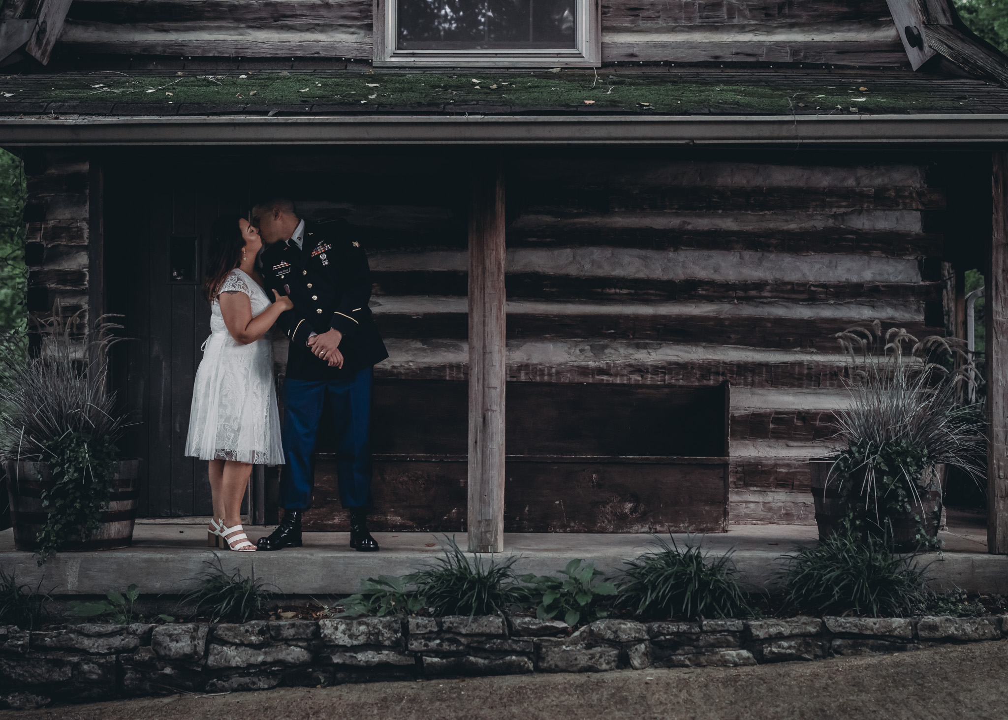 bride and groom kissing in front of tanglewood house