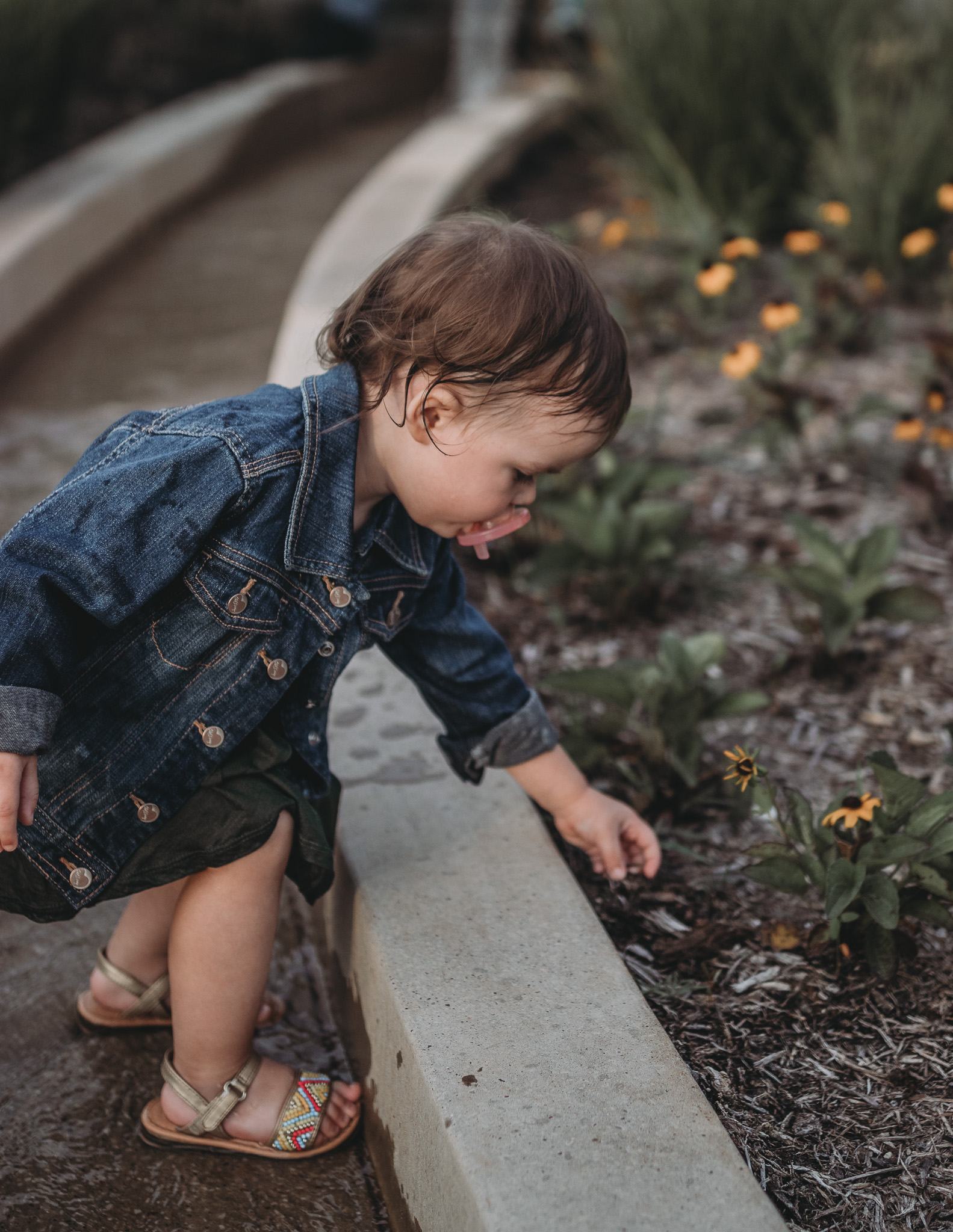 child smelling flowers downtown