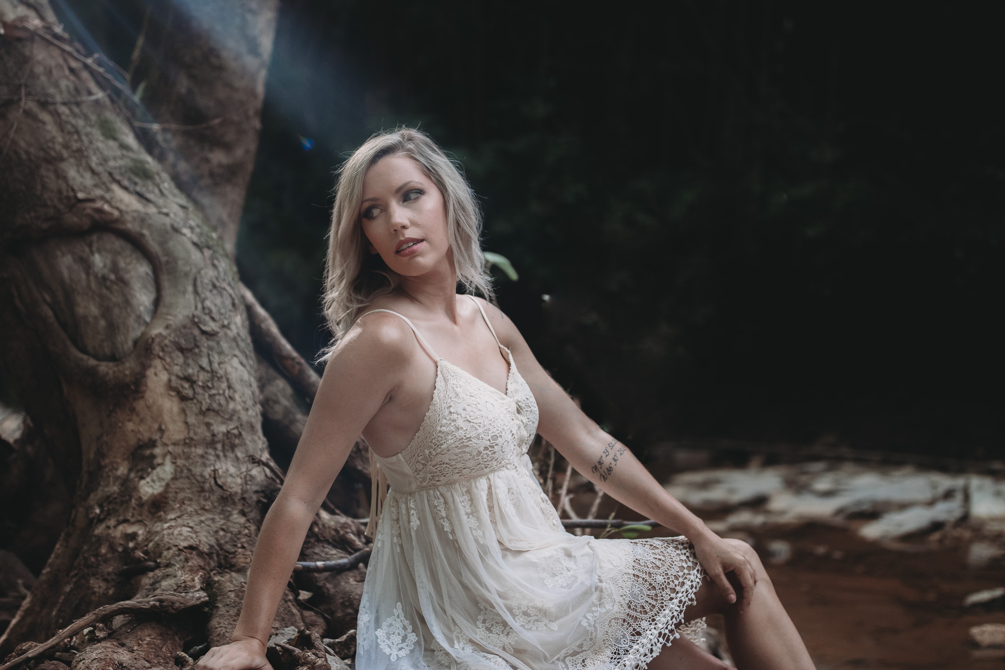 girl sitting on log outdoor boudoir