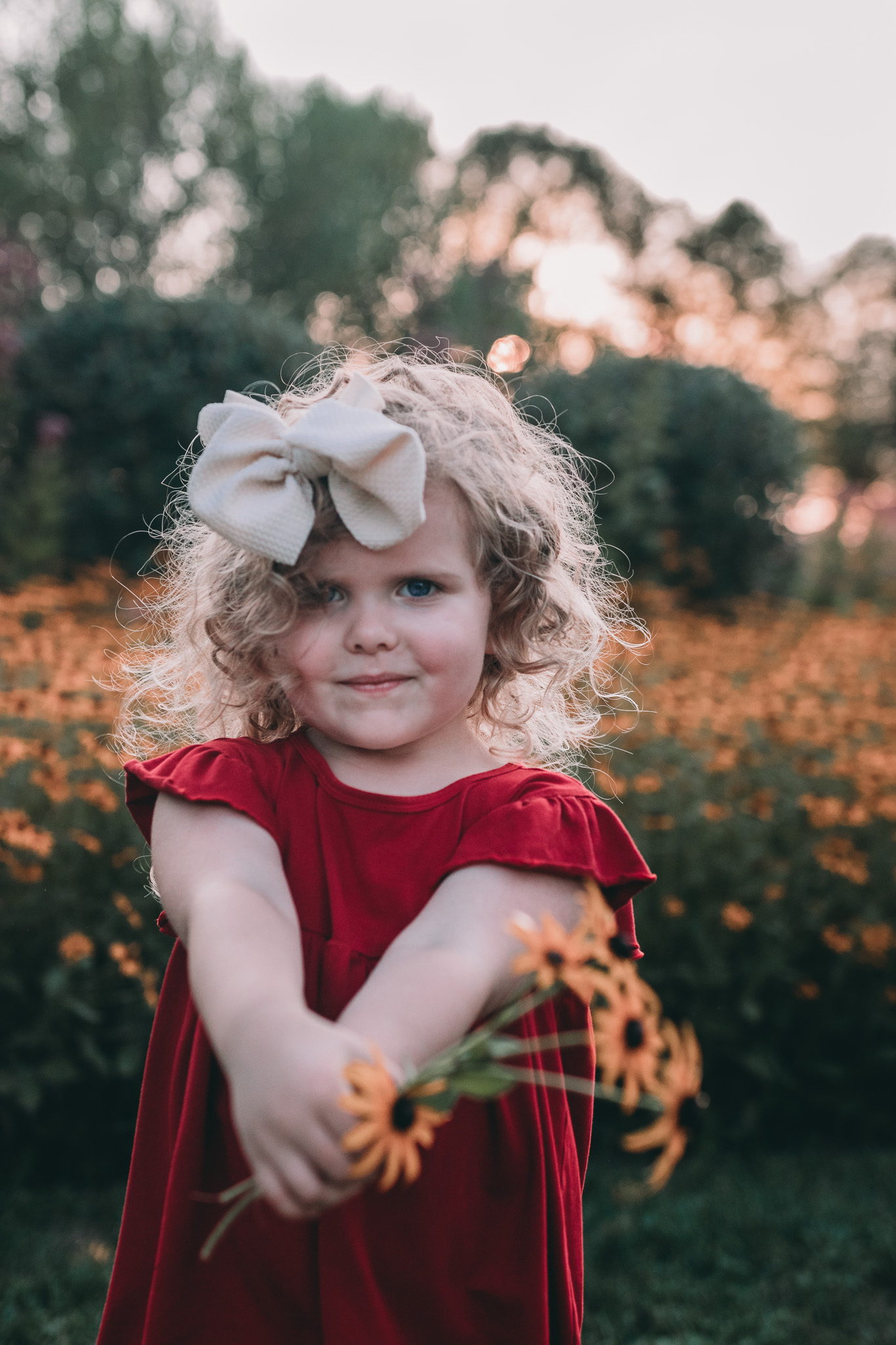 little girl holding out flowers