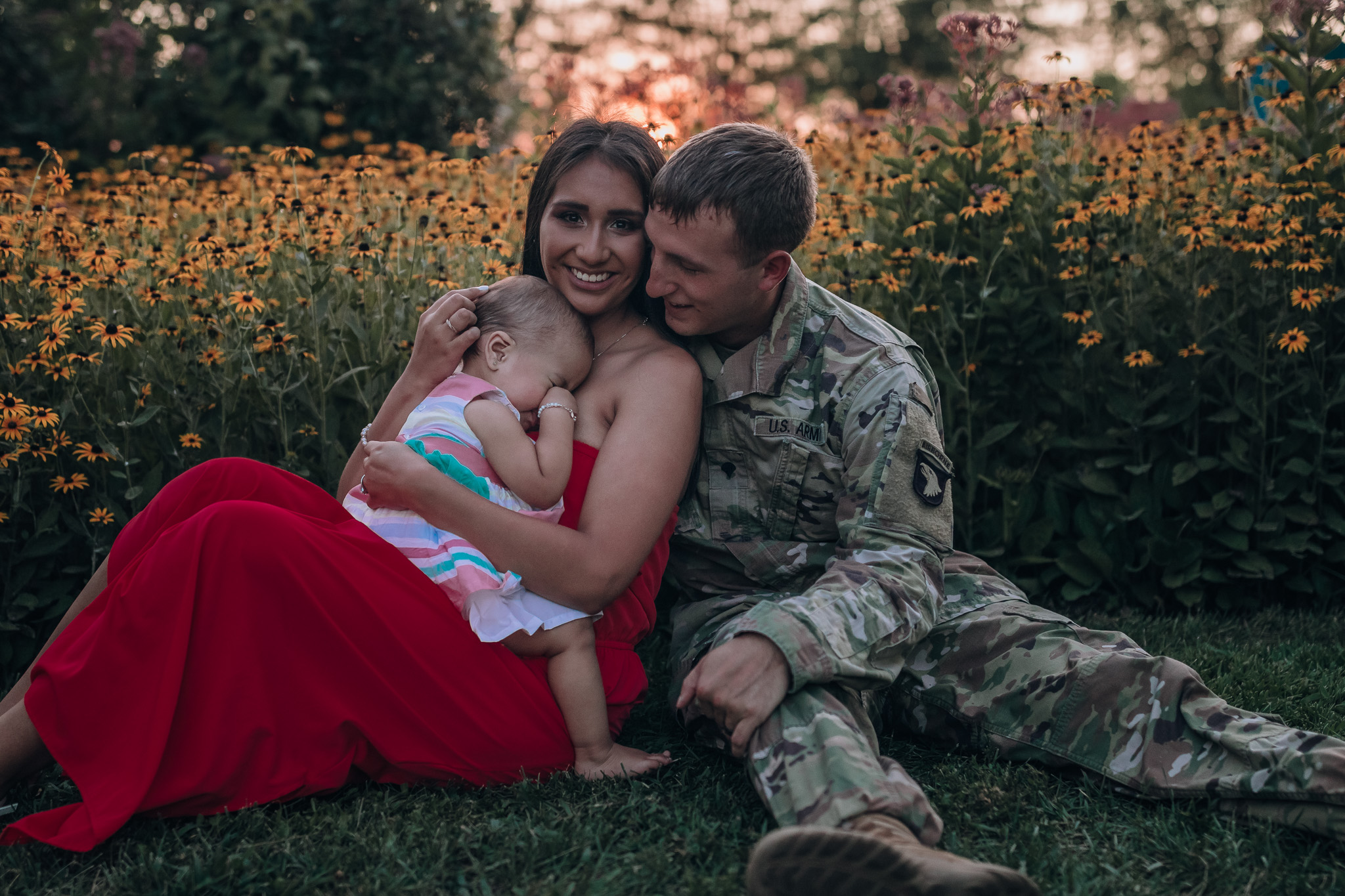 mom holding baby with dad in army uniform
