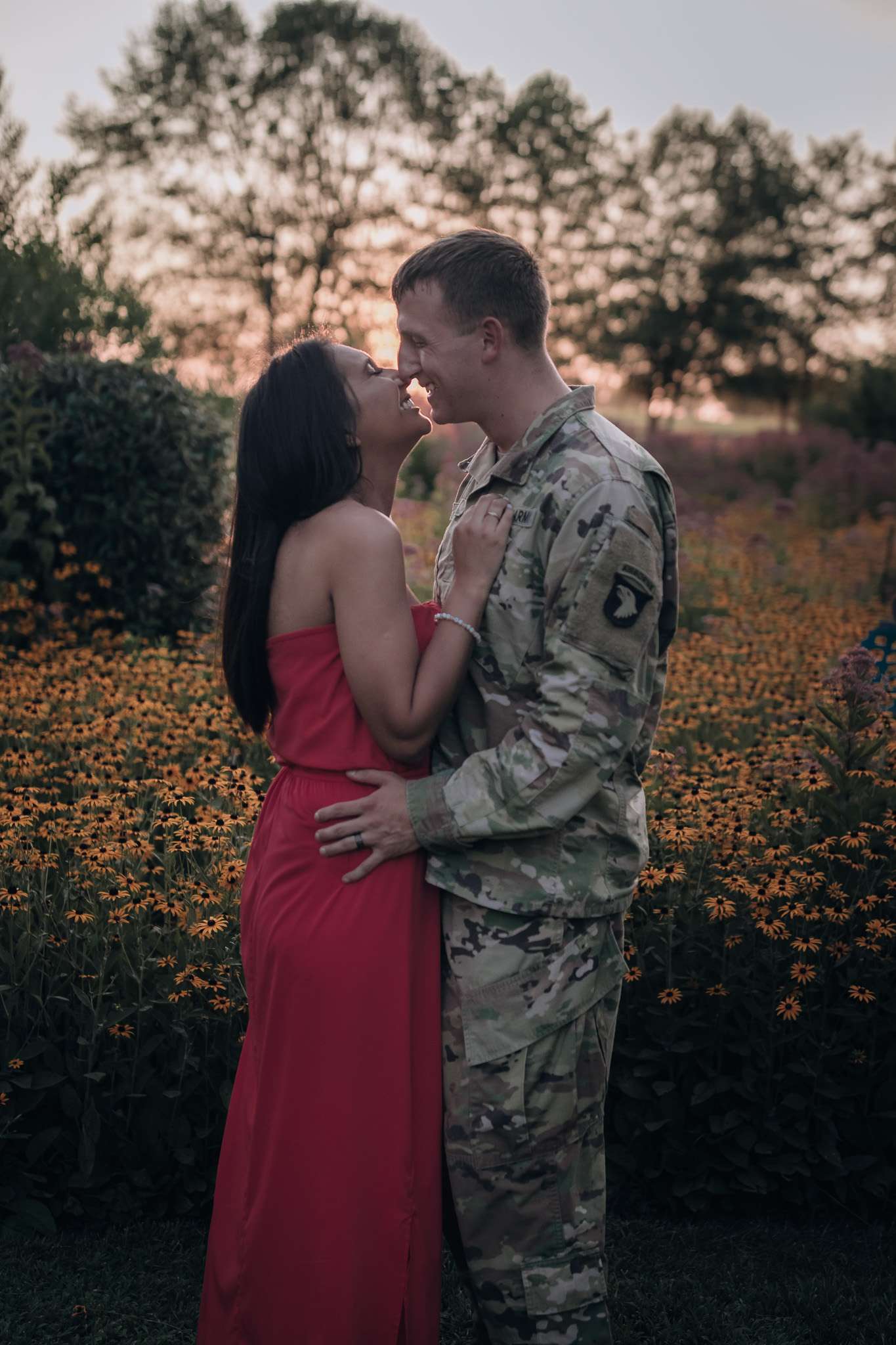 couple kissing at sunset in flowers