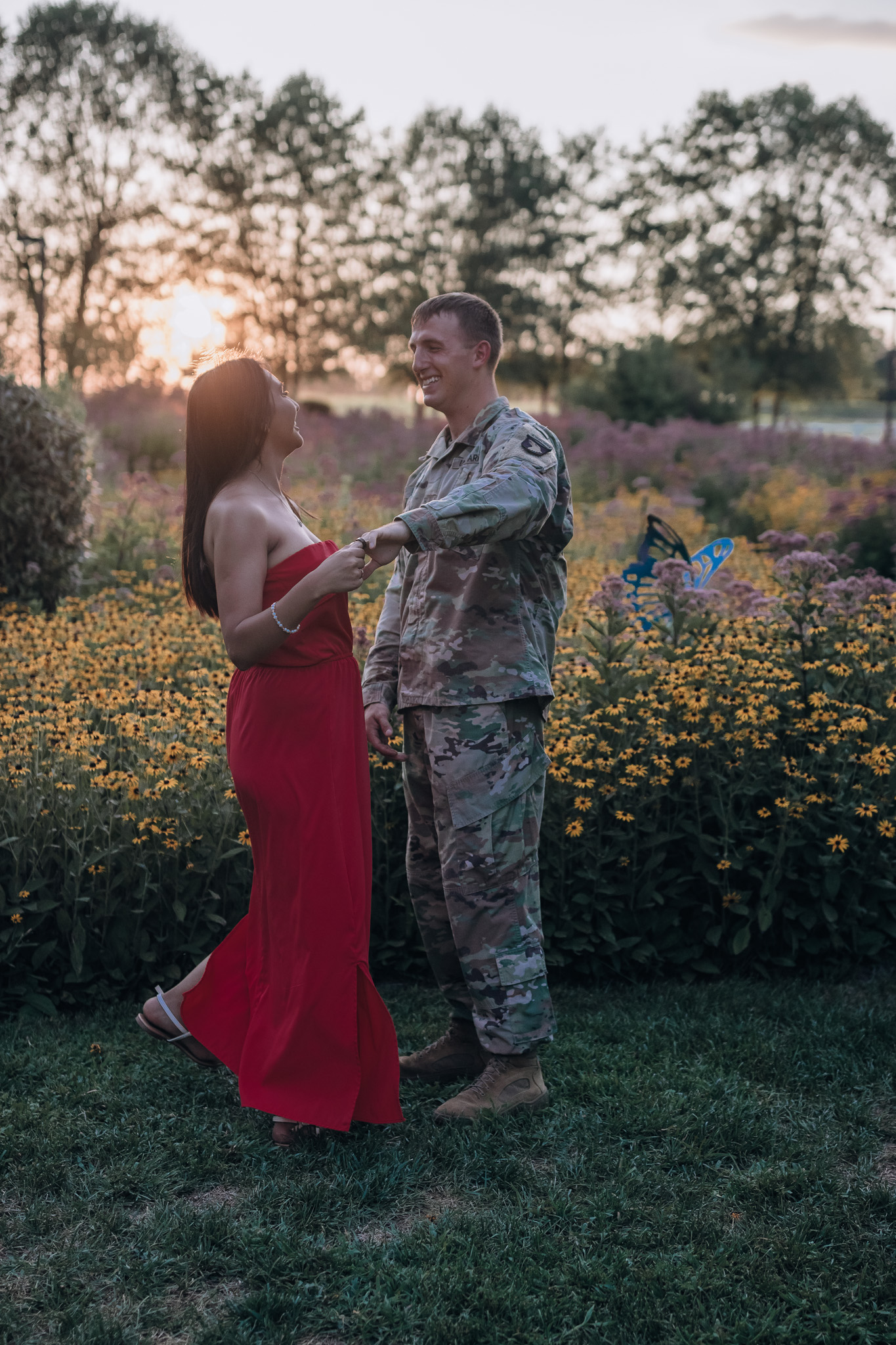 couple dancing in flower field at sunset