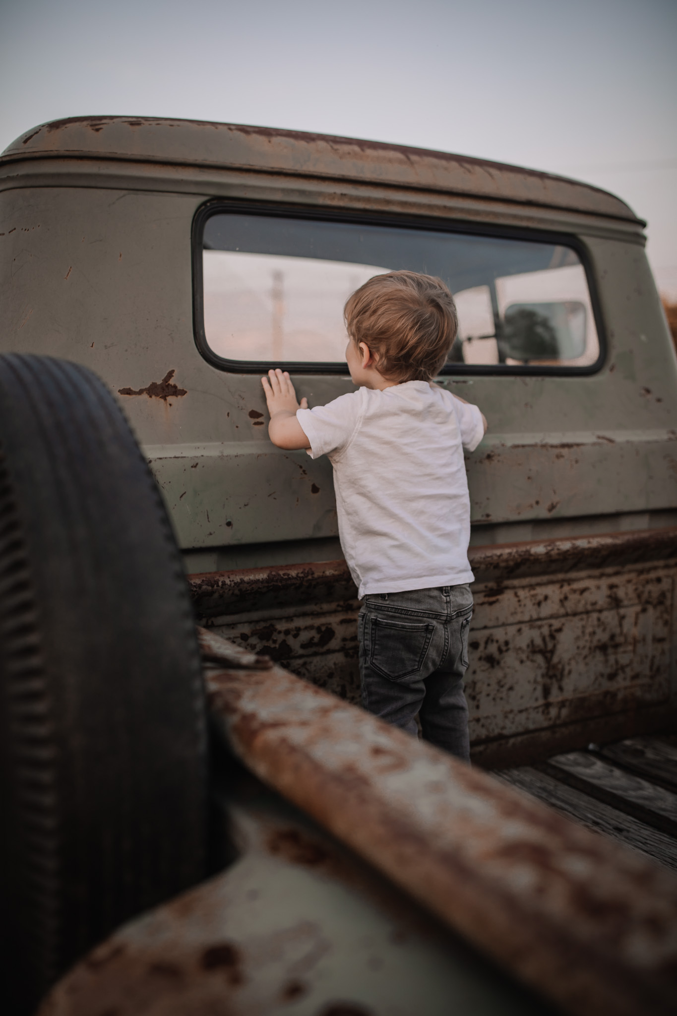 little boy on antique truck bed