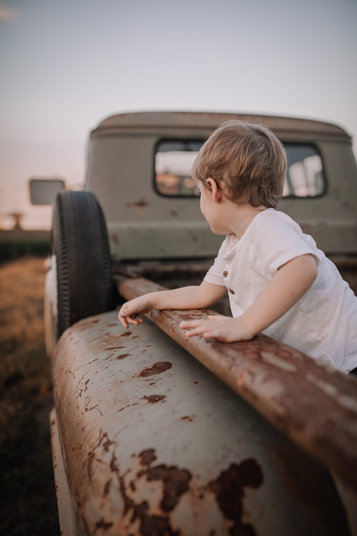 toddler boy playing on vintage truck