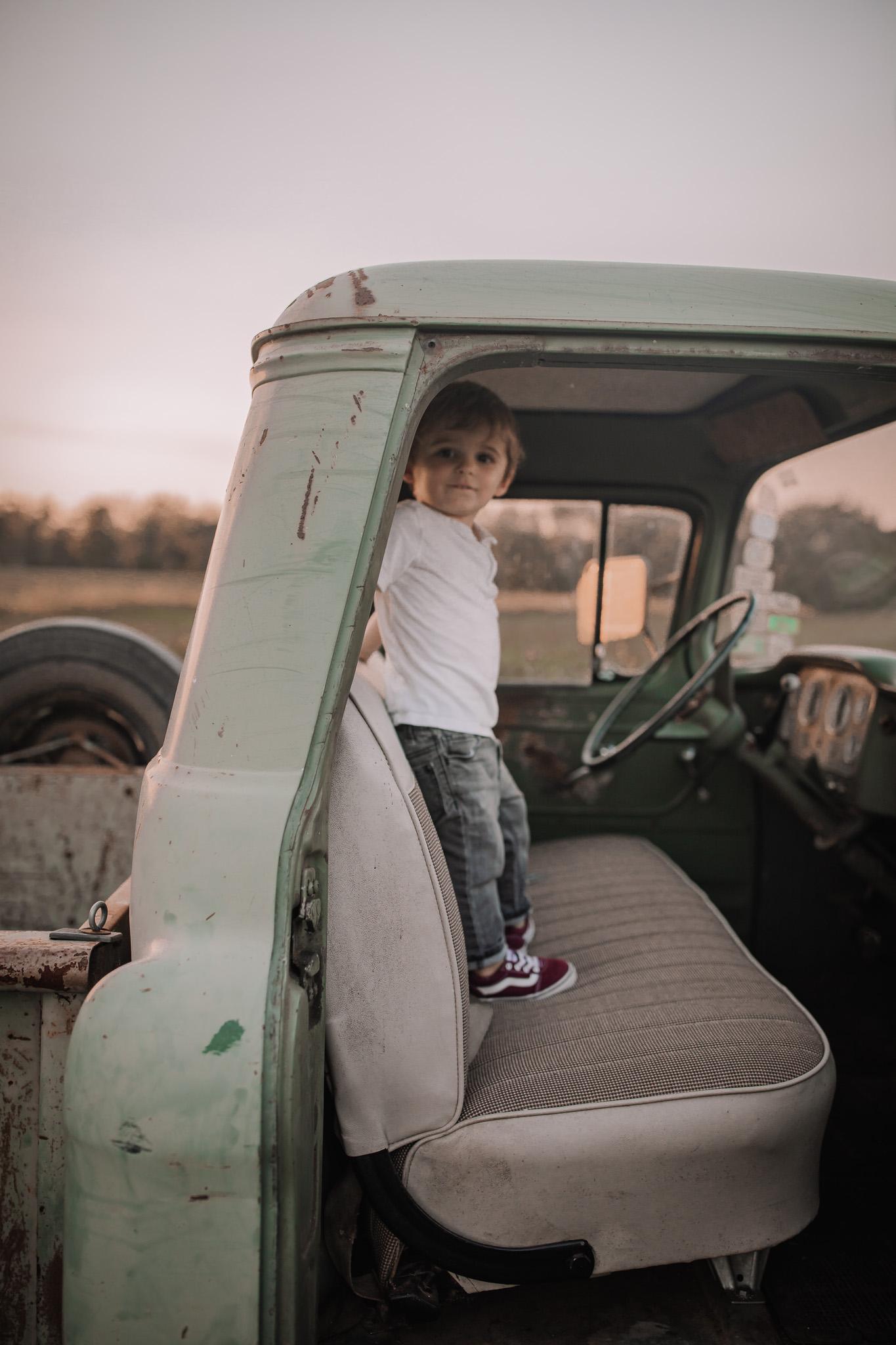 toddler boy standing in vintage truck