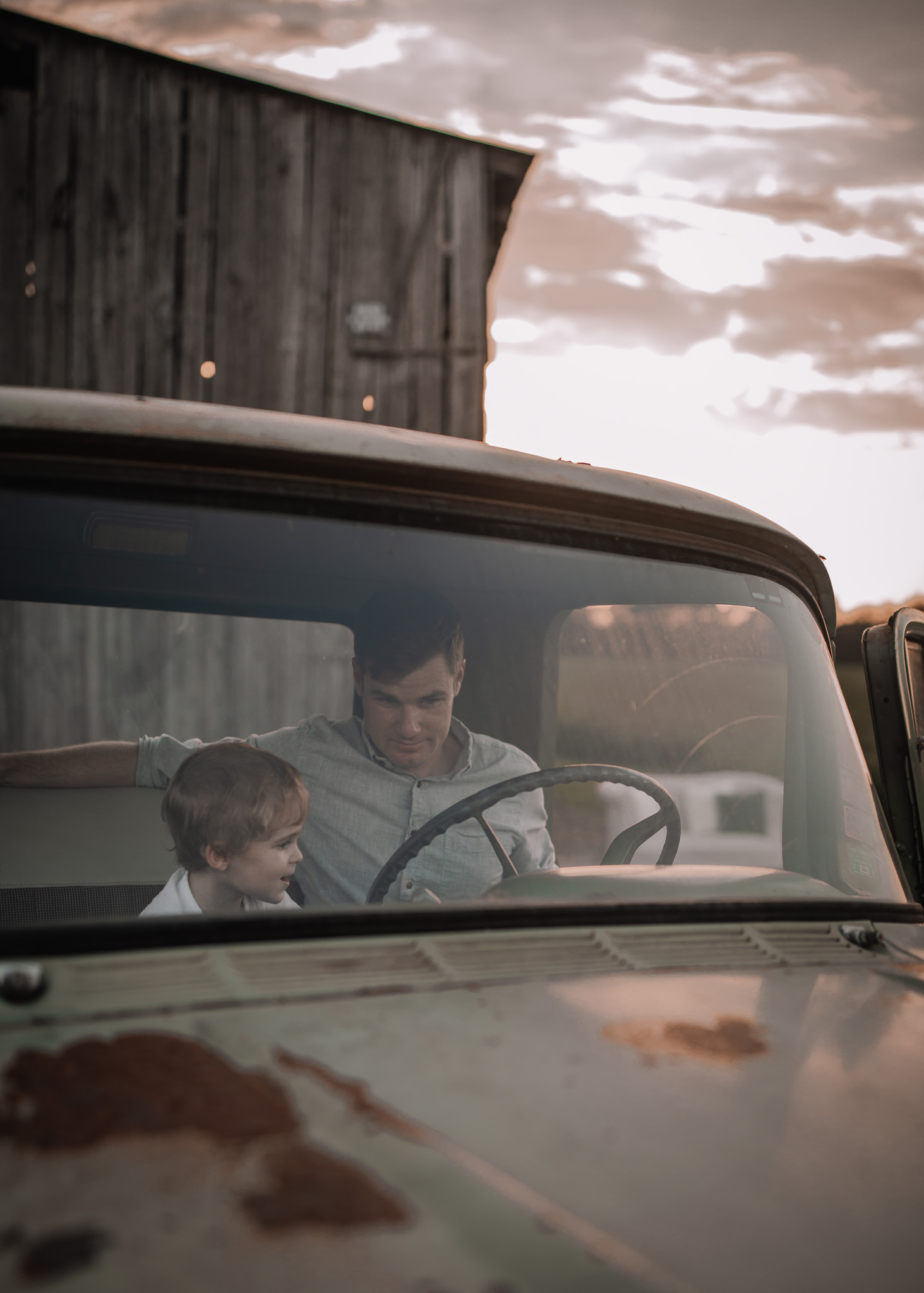 toddler boy and father sitting in vintage truck