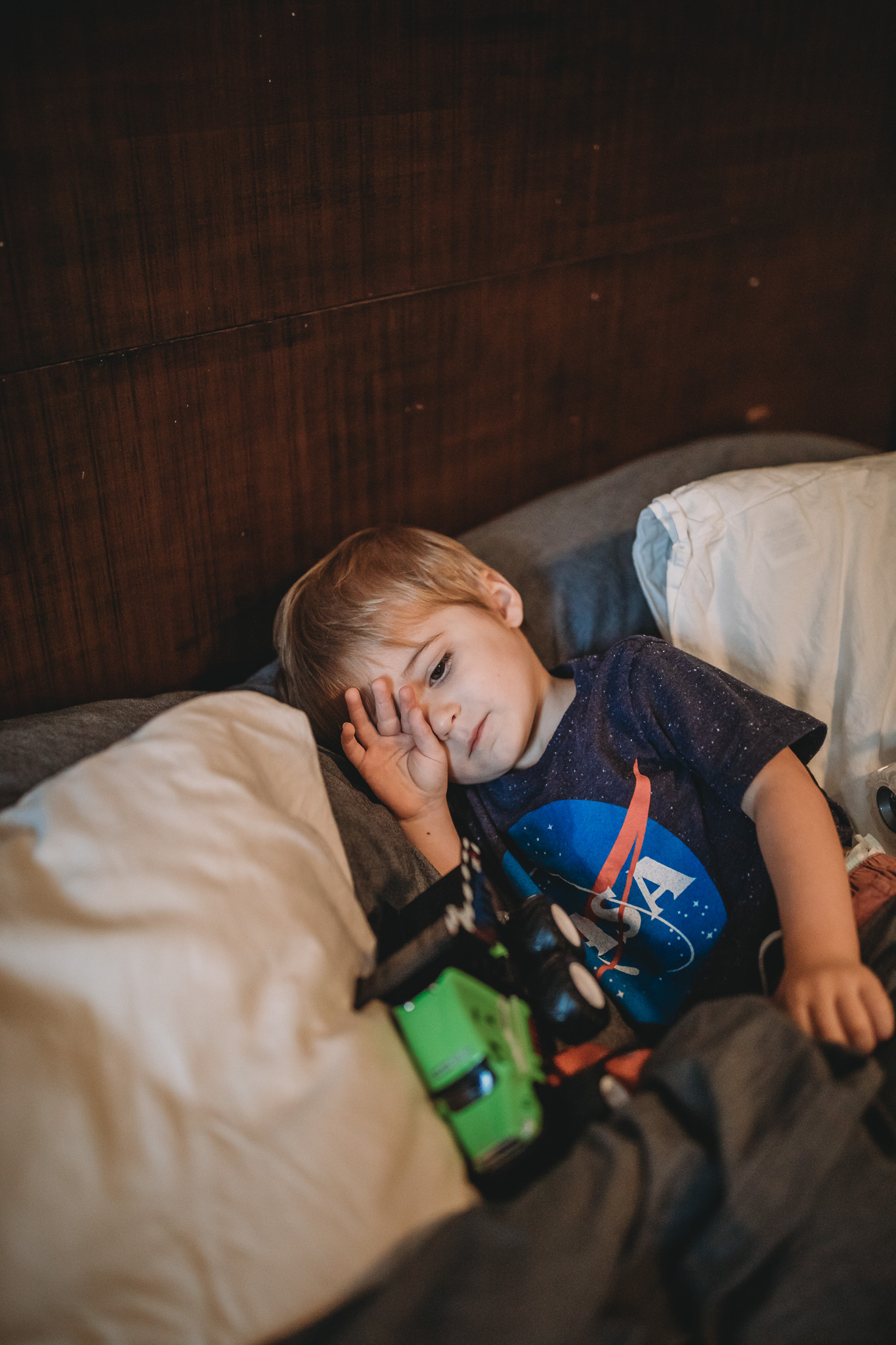 little boy in bed with trucks