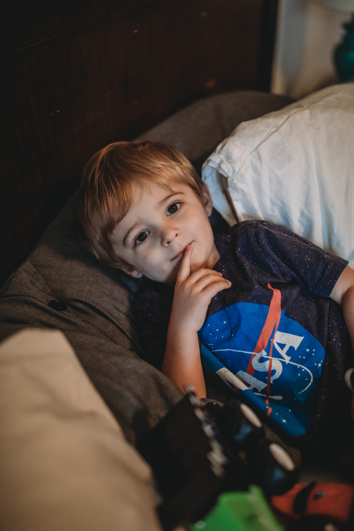 little boy with toys in bed