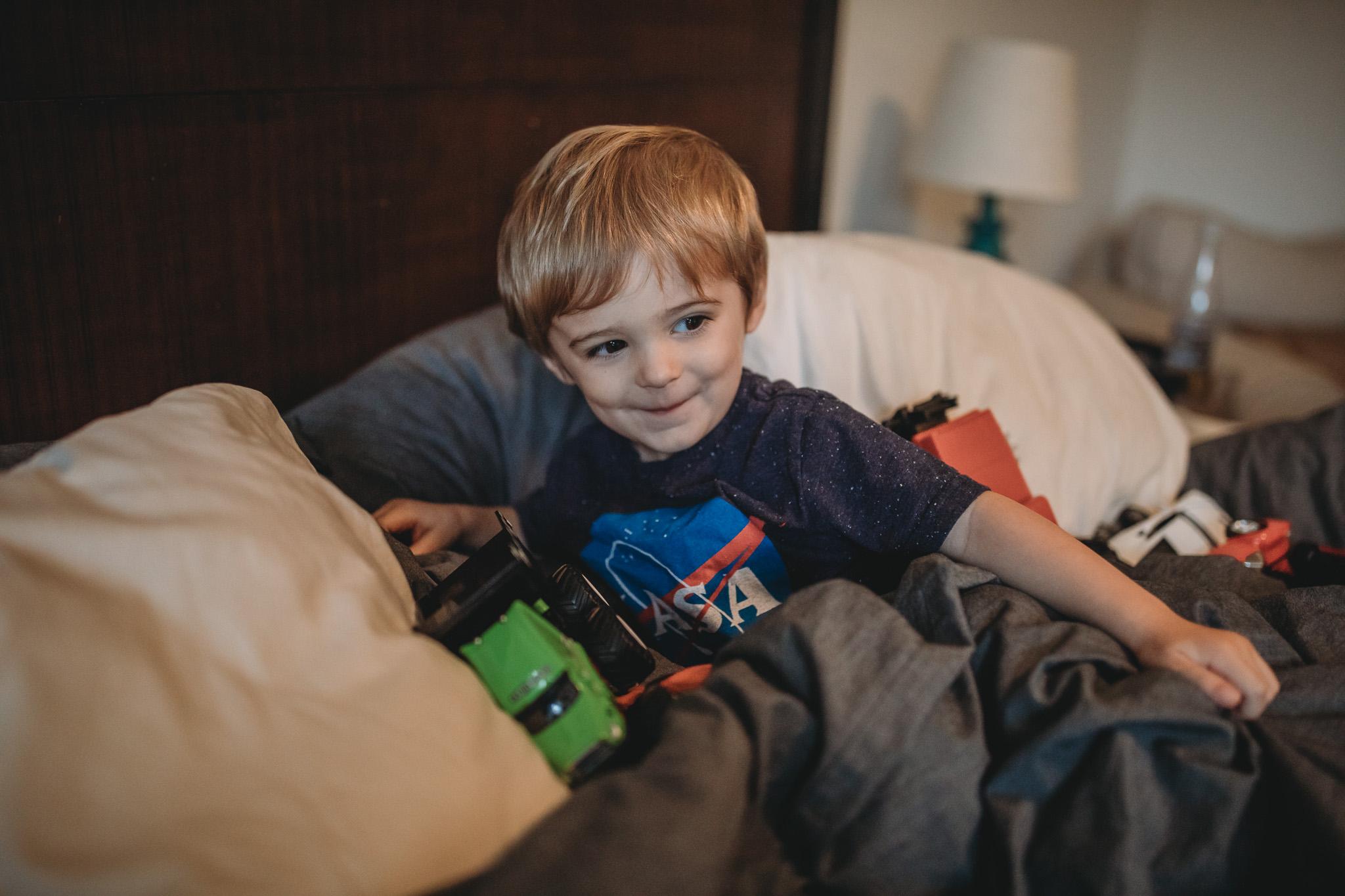 little boy in bed playing