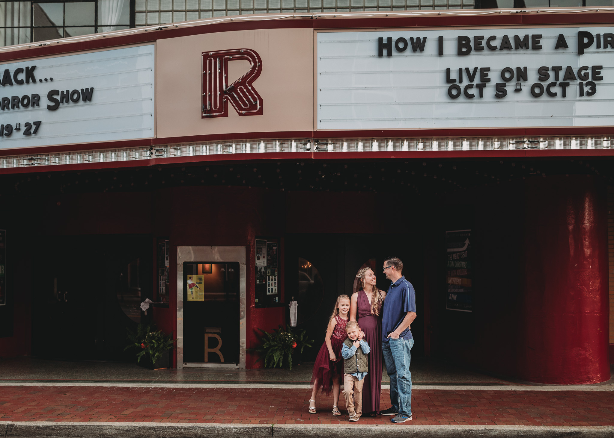 family pose in front of Roxy theater