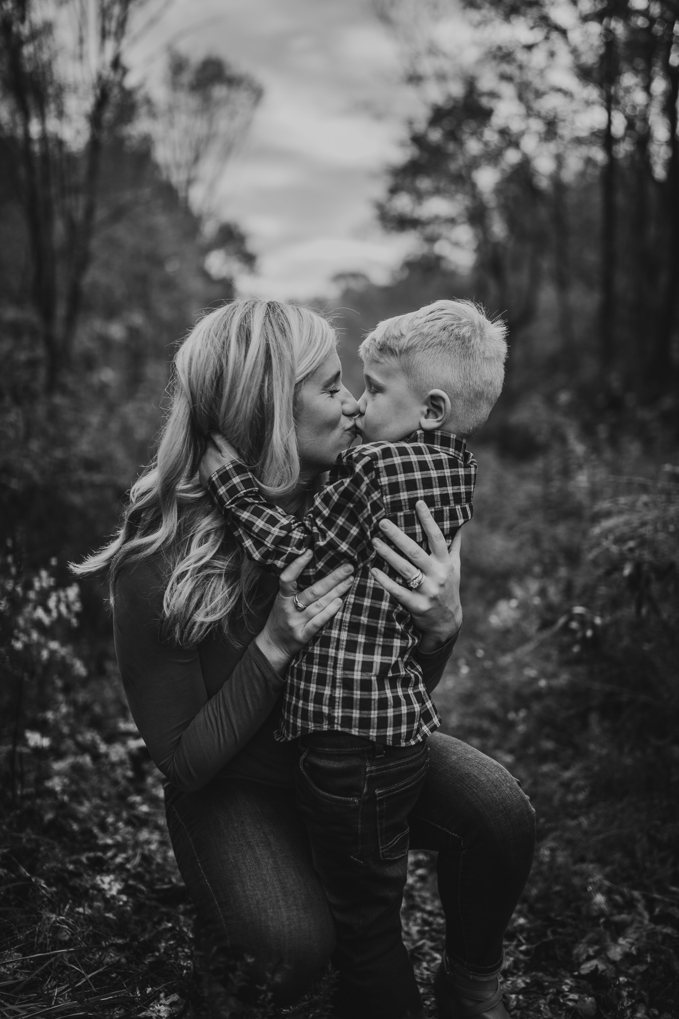toddler boy kissing mom