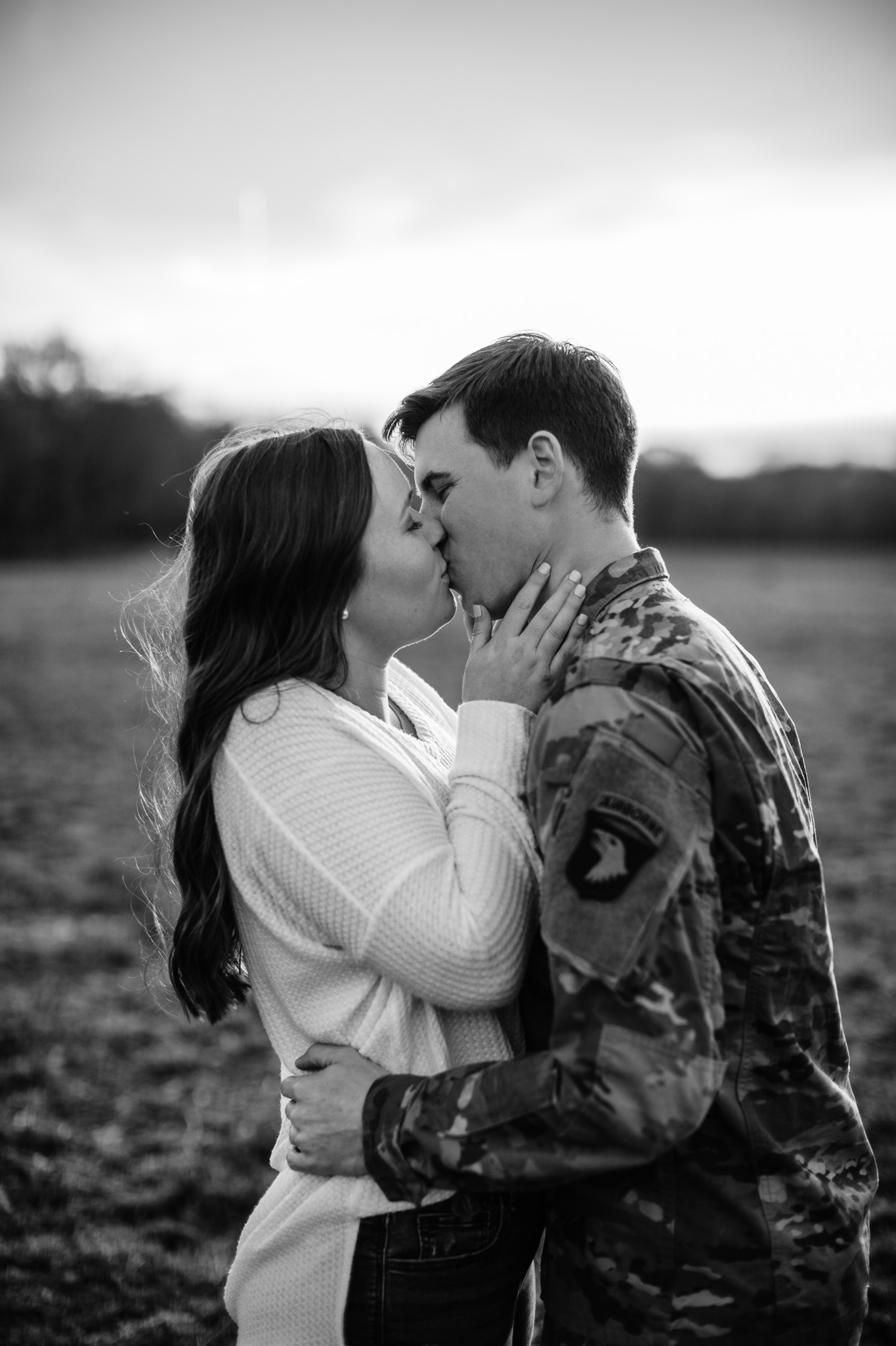 black and white photo of couple kissing with man in uniform