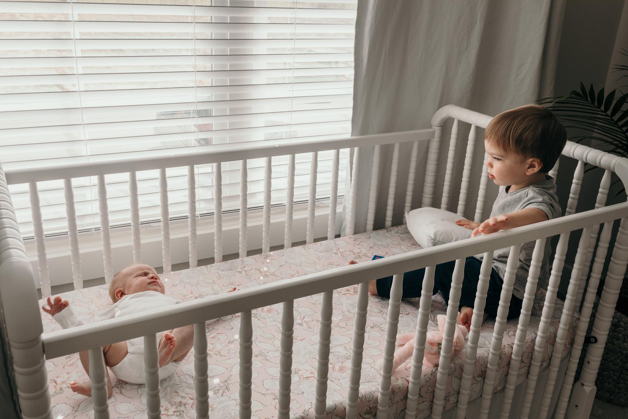 Siblings Playing in Crib